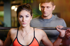 Fitness girl with a barbell working with a trainer. The concept of health, sports Royalty Free Stock Photography