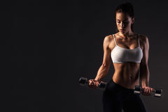Fitness girl. Beautiful athletic girl exercising on a dark background. Young woman with muscular body. Fitness concept royalty free stock photography