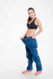 Fitness girl in big jeans showing result of weight loss Stock Photo