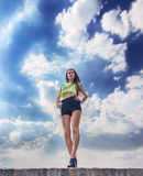 Fitness girl on the blue sky background. Beautiful fitness girl with perfect legs on the blue sky background with clouds stock photo