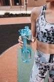 Fitness girl with blue water bottle. royalty free stock photography