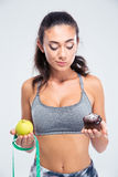 Fitness girl choosing between apple and cake Royalty Free Stock Photo
