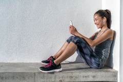 Fitness woman listening to phone music motiivation. Fitness girl choosing music motivation for workout listening to phone app and wearing wearable tech royalty free stock photography
