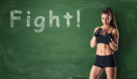 Fitness girl clenching her fists ready to fight on the background of a chalkboard royalty free stock photography