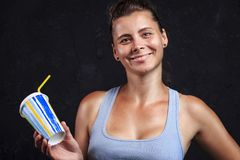 Fitness girl with cocktail after workout. Portrait of smiling young attractive woman. stock photography