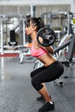 Fitness girl doing barbell squats Stock Photo