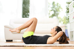 Fitness girl doing crunches at home Royalty Free Stock Images