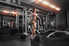 Fitness girl doing exercise with dumbbells in the gym Stock Photos