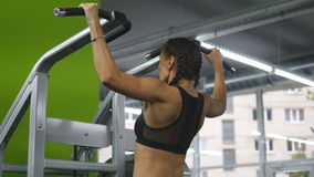 Fitness girl doing pull ups at the gym. Young woman doing exercises on the horizontal bar. Bodyfitness workout. Rear stock footage
