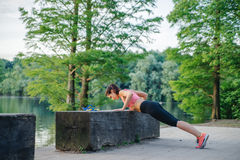 Fitness girl doing push ups outdoor. Fitness girl doing push ups in park Royalty Free Stock Image