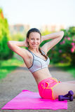Fitness girl doing warm-up routine in the park before running, stretching leg muscles with standing single knee to chest Stock Photo