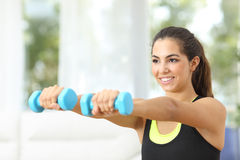 Fitness girl doing weights at home. Happy fitness girl practicing sports doing weights at home Royalty Free Stock Images