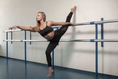 Fit girls preparing legs workout. Leg stretching exercise fitness woman doing warm-up, hamstring muscles stretch. Fitness Girl dressed in black sportswear is stock photography