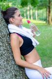 Fitness girl drinking water in summer nature after workout Stock Image