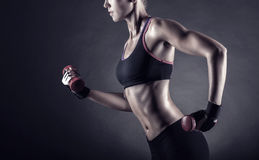 Fitness. Girl with dumbbells on a dark background Royalty Free Stock Images