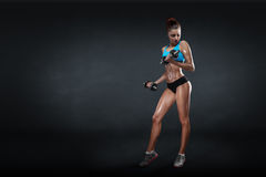 Fitness girl with dumbbells on a dark background Royalty Free Stock Photo