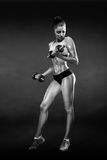 Fitness girl with dumbbells on a dark background Stock Image