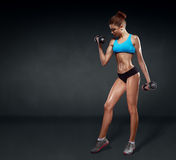 Fitness girl with dumbbells on a dark background Stock Photos