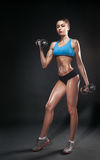 Fitness girl with dumbbells on a dark background Stock Images