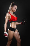 Fitness girl with dumbbells on a dark background Stock Photo