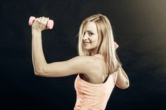 Fitness girl with dumbbells flexing muscles in gym. Fitness, sport, training and lifestyle concept. Fit woman with dumbbells flexing muscles in gym. Muscular Royalty Free Stock Photo