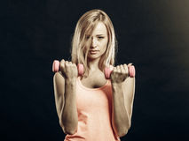 Fitness girl with dumbbells flexing muscles in gym. Fitness, sport, training and lifestyle concept. Fit woman with dumbbells flexing muscles in gym. Muscular Royalty Free Stock Photos