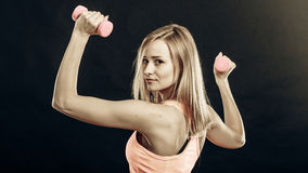 Fitness girl with dumbbells flexing muscles in gym Royalty Free Stock Images