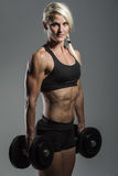 Fitness girl with dumbells. A young and very fit woman training with dumbells Royalty Free Stock Photography