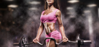 Fitness girl exercising with barbell in gym Stock Image