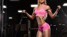 Fitness girl exercising with barbell in gym Stock Images