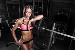 Fitness girl exercising with barbell in gym Stock Photography