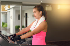 Fitness girl exercising on a cardio machine. And Listening to music for relaxation in morning Royalty Free Stock Images
