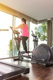 Fitness girl exercising on a cardio machine Royalty Free Stock Images