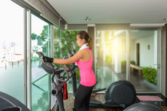 Fitness girl exercising on a cardio machine. And smiling in morning Stock Photography