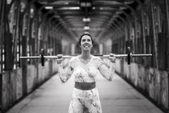 Fitness girl exercising with dumbbell on street. Beautiful brunette woman doing sports on an iron bridge stock photography