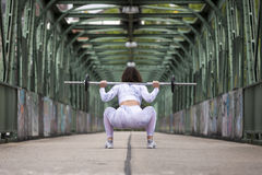 Fitness girl exercising with dumbbell on street stock photography