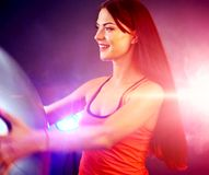 Fitness girl exercising in gym with fitball. Fitness girl exercising in gym with ball. Woman with fitball works in multi-colored rays of sport room. Portrait of Stock Photo