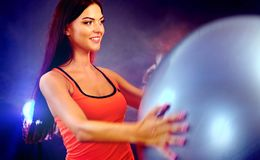 Fitness girl exercising Swiss ball in fitball gym. Body ball for upper-body russian twist in fitness girl hands royalty free stock image