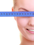 Fitness girl fit woman covering her eyes with measuring tape Stock Photography