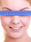 Fitness girl fit woman covering her eyes with measuring tape Royalty Free Stock Photography