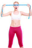 Fitness girl fit woman covering her eyes with measuring tape Royalty Free Stock Image
