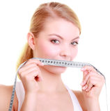 Fitness girl fit woman covering her mouth with measuring tape. Body care diet and weight loss concept. Fitness girl sporty woman covering her mouth lips with Royalty Free Stock Images