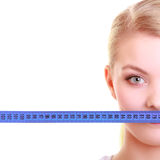 Fitness girl fit woman covering her mouth with measuring tape Stock Image