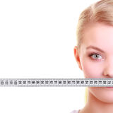 Fitness girl fit woman covering her mouth with measuring tape Royalty Free Stock Image