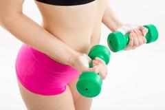 Fitness girl with green dumbbells. Fitness girl in pink pants is coaching with green dumbbells, with white background Stock Image