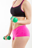 Fitness girl with green dumbbells. Fitness girl in pink pants is coaching with green dumbbells, with white background Royalty Free Stock Photography