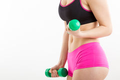 Fitness girl with green dumbbells. Fitness girl in pink pants is coaching with green dumbbells, with white background Royalty Free Stock Images