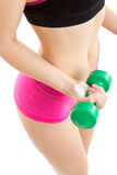 Fitness girl with green dumbbells. Fitness girl in pink pants is coaching with green dumbbells, with white background Royalty Free Stock Image
