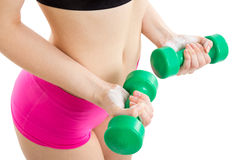 Fitness girl with green dumbbells. Fitness girl in pink pants is coaching with green dumbbells, with white background Royalty Free Stock Photo