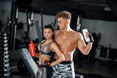 Fitness girl and guy model with a shaker relax in the gym. Slim sporty woman and man in sportswear clothes royalty free stock photos